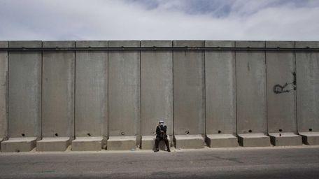 A Palestinian man pauses near the Qalandia checkpoint