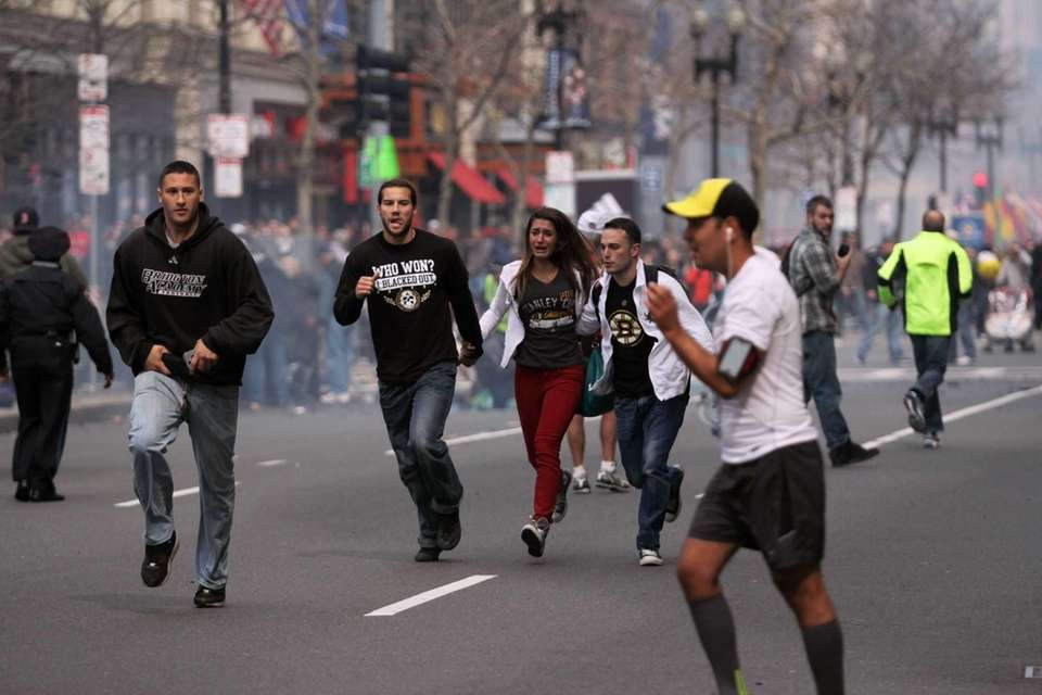 People react to an explosion at the 2013