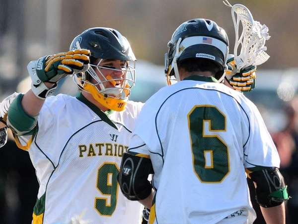 Ward Melville's Jake Kepes, left, congratulates Christian Mazzone after he scored a goal during the first period of a Suffolk boys lacrosse game against Smithtown West. (April 15, 2013)