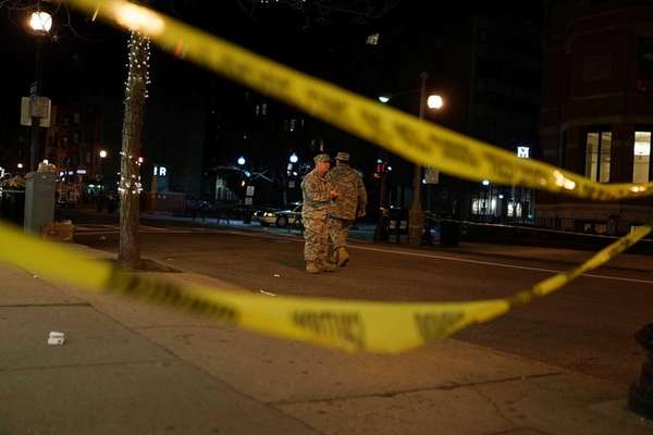 National Guard soldiers stand near the scene of