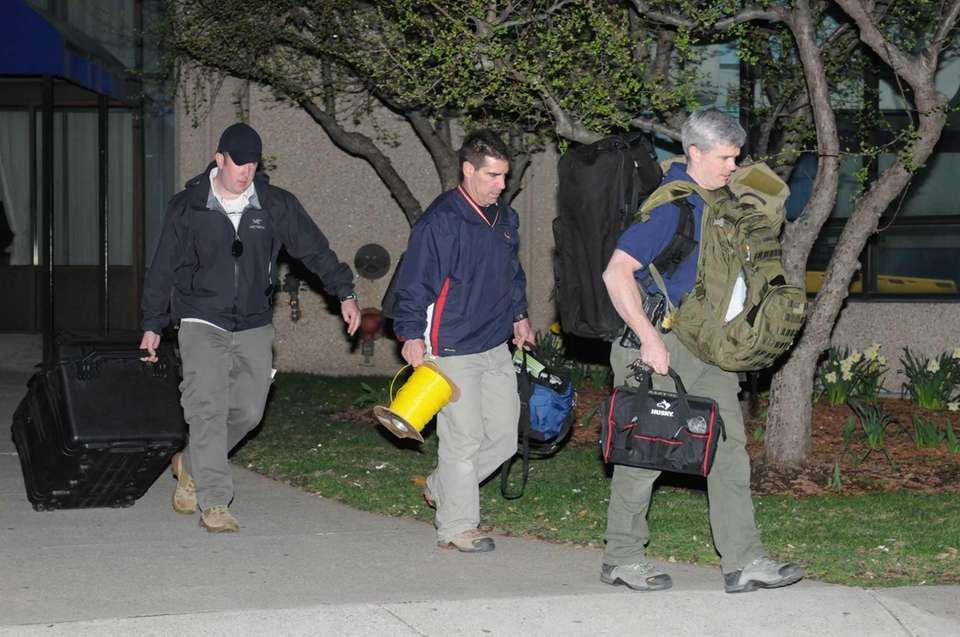Police and federal officials exit an apartment complex