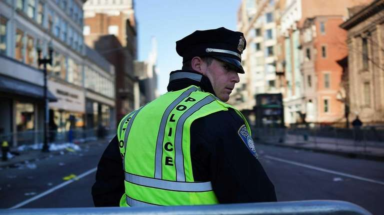 A Boston police officer stands near the scene