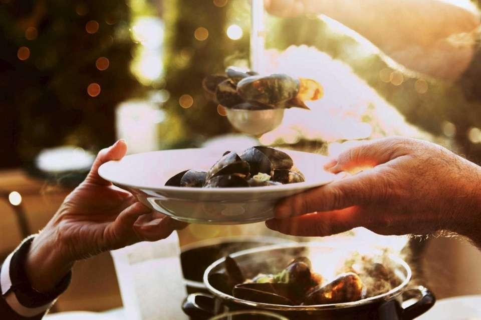 Patrons share a bowl of mussels at Waterzooi