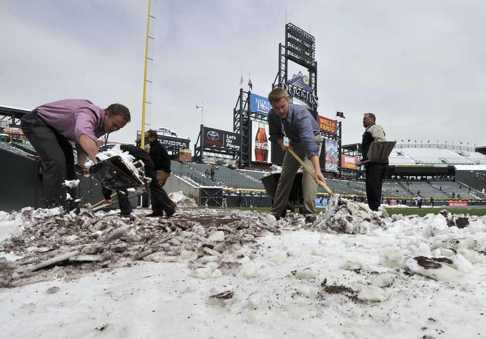 Coors Field grounds crew and stadium employees shovel