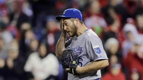 Kansas City Royals relief pitcher Greg Holland wipes