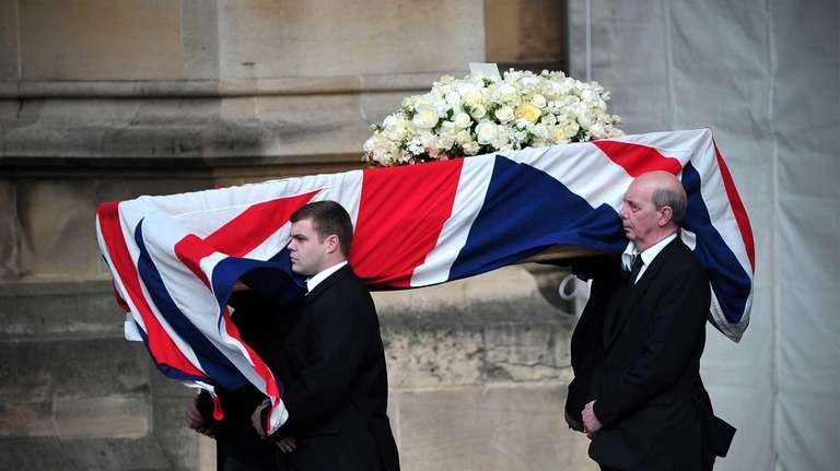 Pallbearers carry the coffin of former British prime