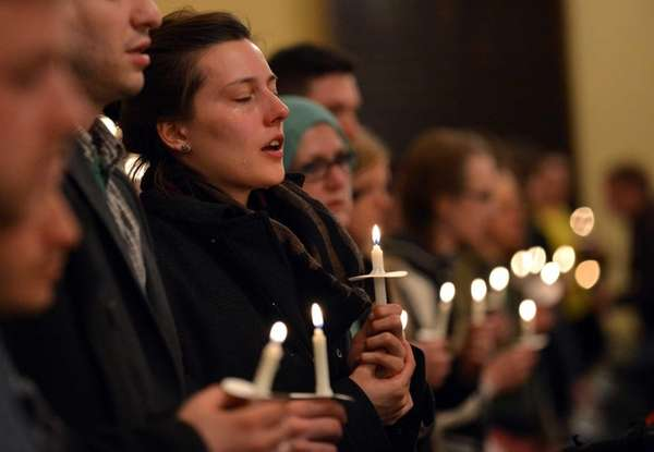 A woman cries during a candlelight interfaith service