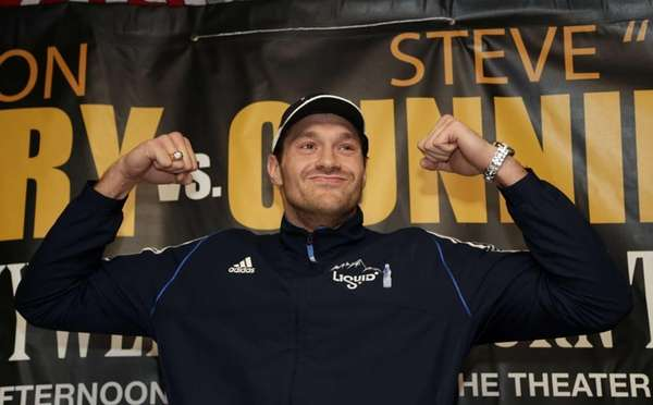 Tyson Fury poses for pictures during a news