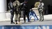 Officials in tactical gear stand guard behind a