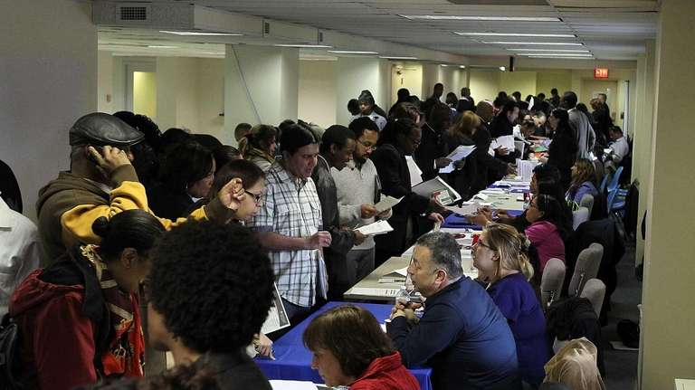 Job seekers meet with recruiters during a job