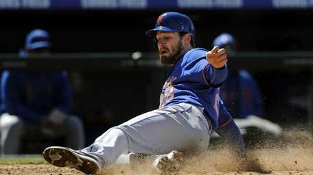 Daniel Murphy slides into home plate to score