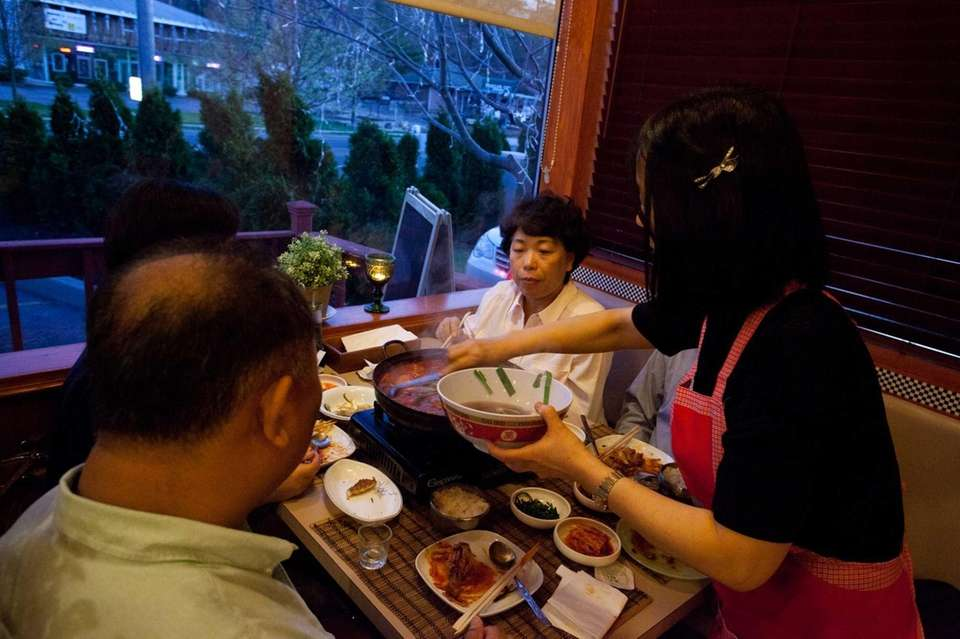 Owner Kyeonghee Moon serves a table of diners