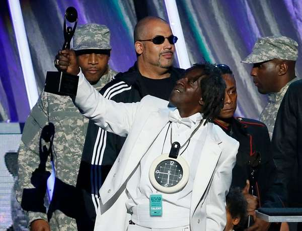 Flavor Flav holds an award on stage as