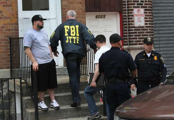 FBI agent enters the apartment building door of