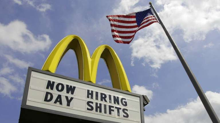 A sign advertising job openings outside a McDonalds