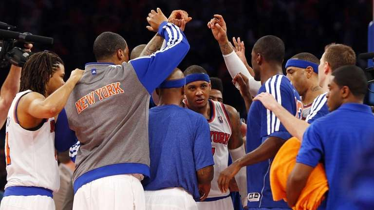 The Knicks huddle around Carmelo Anthony after defeating