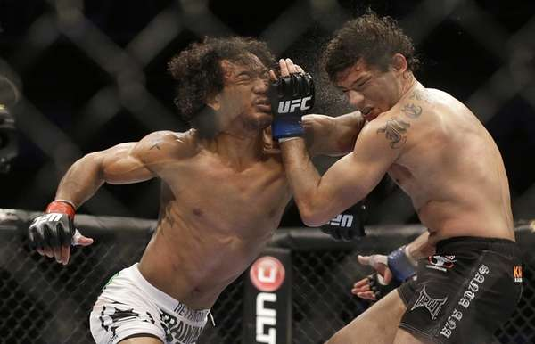 Benson Henderson, left, punches Gilbert Melendez during the