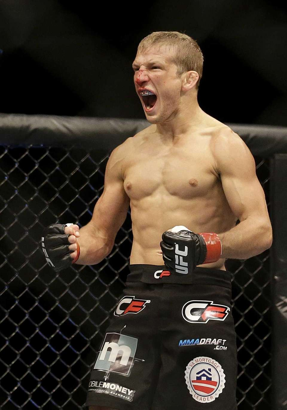 T.J. Dillashaw celebrates after beating Hugo Viani during
