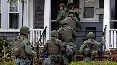 Heavily armed police officers perform a house-to-house search