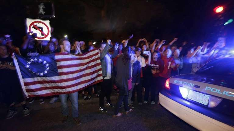 A police cruiser drives by as people react
