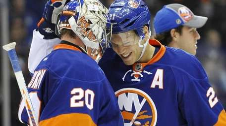 Evgeni Nabokov is congratulated by Kyle Okposo, right,
