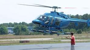 A helicopter lands at East Hampton Airport on