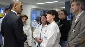 President Barack Obama talks with staff at Massachusetts