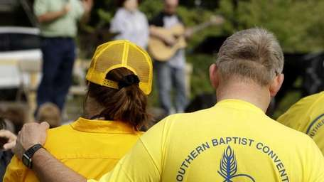 Volunteer relief workers listen to a service for