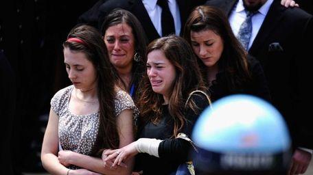 Mourners walk out of St. Joseph Catholic Church