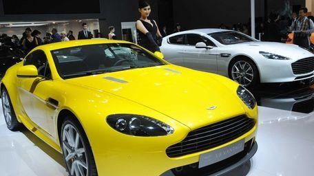 A model poses next to a Aston Martin