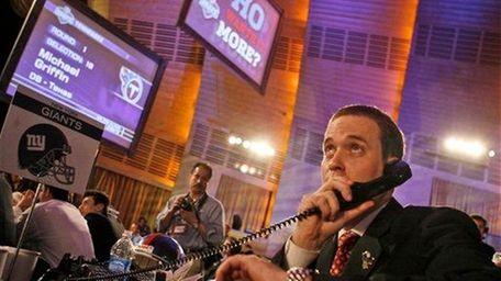 A Giants draft representative talks on the phone
