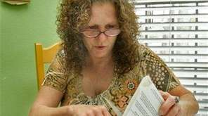 Kathy Lovelace looks over mortgage documents at her