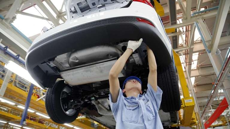 A worker assembles a vehicle on an assembly