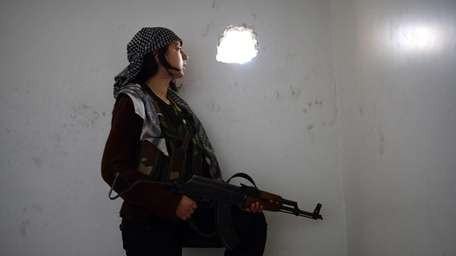 A Kurdish female fighter observes the movement of