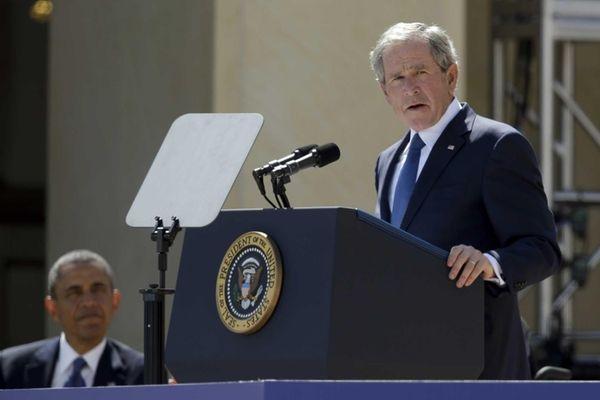 President Barack Obama listens as former President George