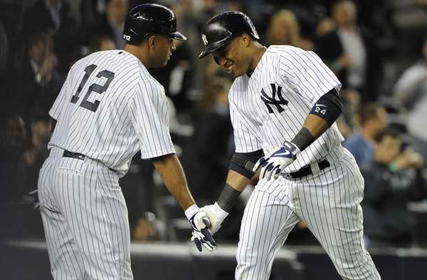 Vernon Wells congratulates Robinson Cano on his three-run