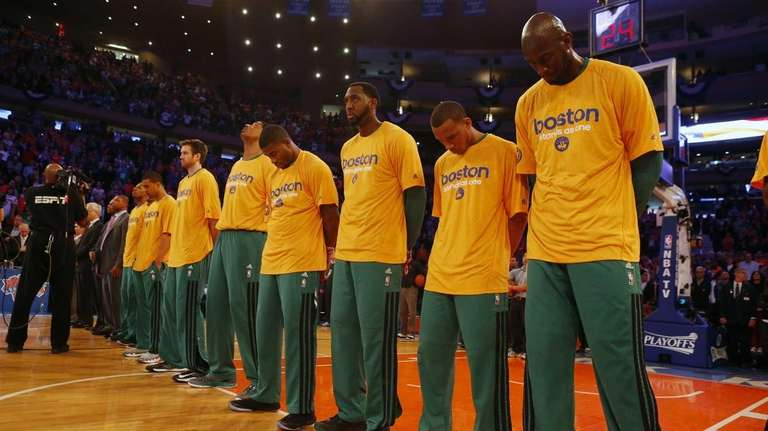 The Boston Celtics stand during the national anthem