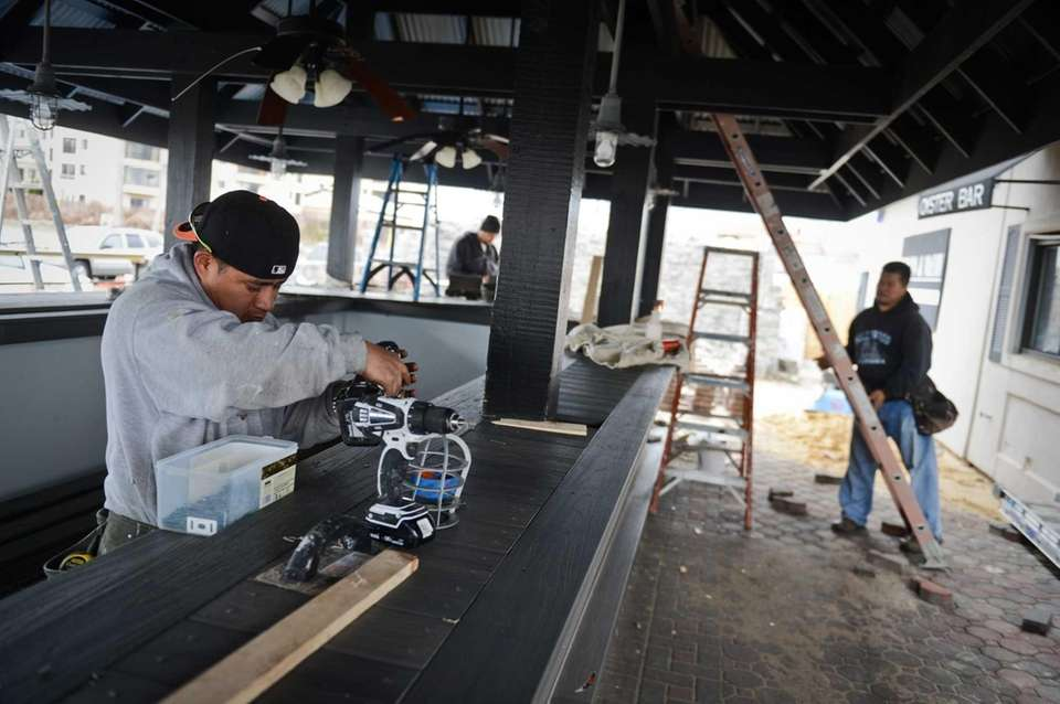 Carlos Rodriguez, left, of Dover construction, renovates the