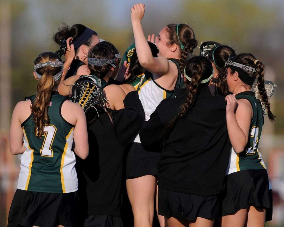 Ward Melville varsity girls' lacrosse teammates celebrate after