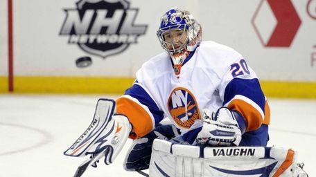 Islanders goaltender Evgeni Nabokov eyes the puck during