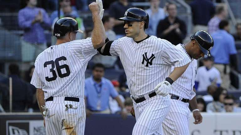 Yankees' Kevin Youkilis congratulates Travis Hafner on his