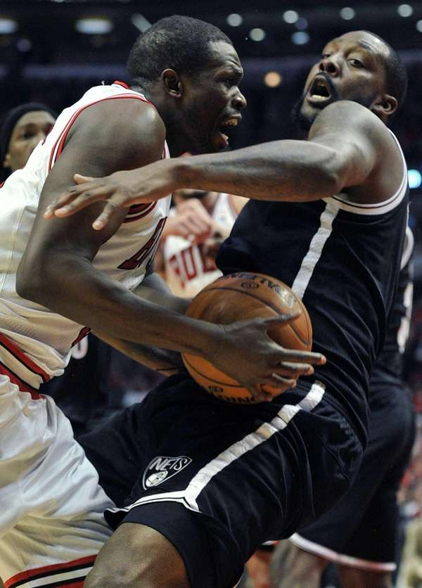 Chicago Bulls' Luol Deng, left, drives to the