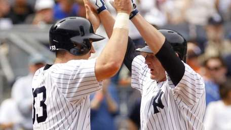 Lyle Overbay is greeted by Travis Hafner after