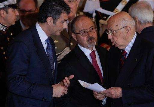 Unidentified aides give Italian President Giorgio Napolitano the