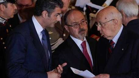Unidentified aides give Italian President Giorgio Napolitano the