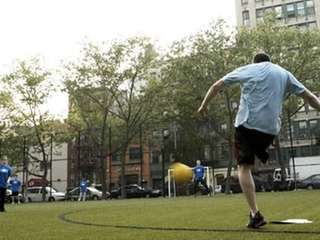 Adults play summer kickball.
