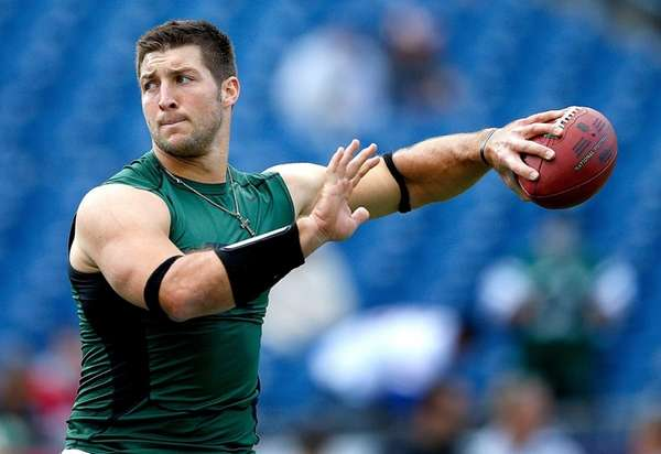 Tim Tebow completes drills before a game against