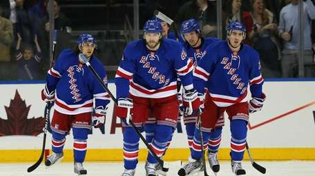 Rick Nash, center, returns to the bench following