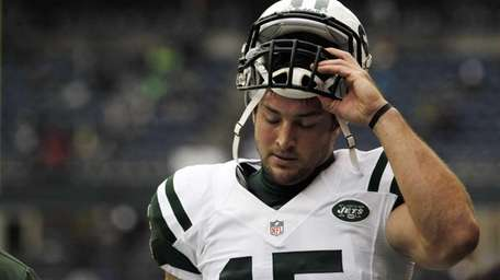 Tim Tebow stands on the field before a