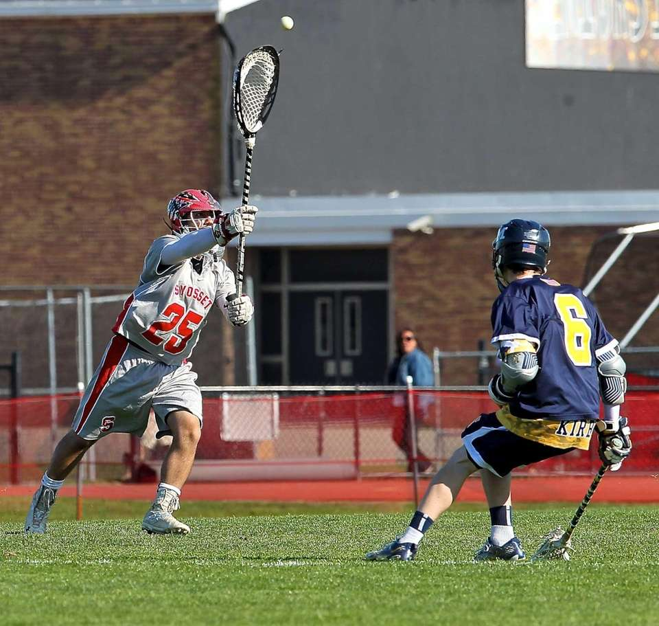 Syosset goalie Ryan Feit moves the ball past